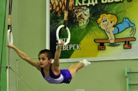 A young boy competes on rings at a competition in Russia.